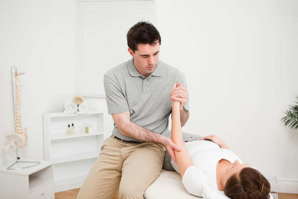 patient is at a chiropractor learning about Fibromyalgia Symptoms and how chiropractic care can help her manage it